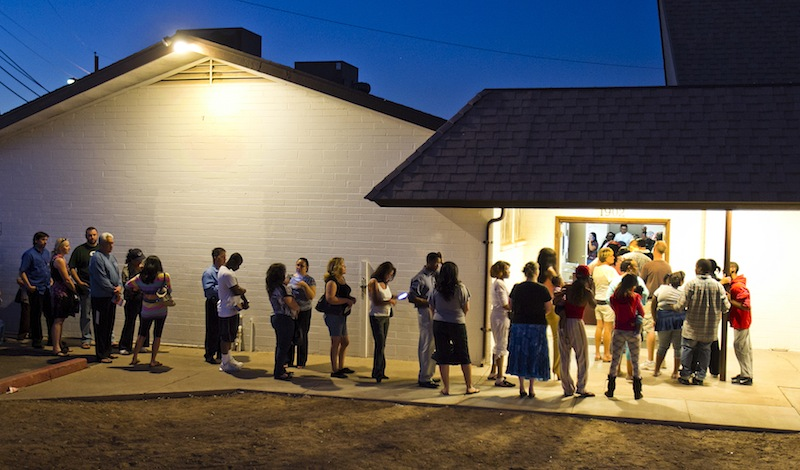 """People wait in line to vote at polling place located in a church in Phoenix in this Nov. 6, 2012, file photo. The Supreme Court ruled Monday, June 17, 2013, that states cannot on their own require would-be voters to prove they are U.S. citizens before using a federal registration system designed to make signing up easier. The justices voted 7-2 to throw out Arizona's voter-approved requirement that prospective voters document their U.S. citizenship in order to use a registration form produced under the federal """"Motor Voter"""" voter registration law. (AP Photo/The Arizona Republic, Tom Tingle) AZR"""