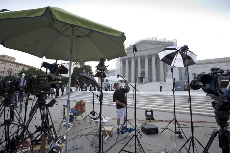 TV crews wait outside the Supreme Court in Washington as key decisions are announced Monday.