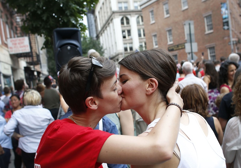 Members of the LGBT community and their supporters gather to celebrate two decisions by the U.S. Supreme Court, one to invalidate parts of the Defense of Marriage Act and another to uphold a lower court ruling that struck down California's controversial Proposition 8, during a rally in New York's Greenwich Village, Wednesday, June 26, 2013. (AP Photo/Jason DeCrow)