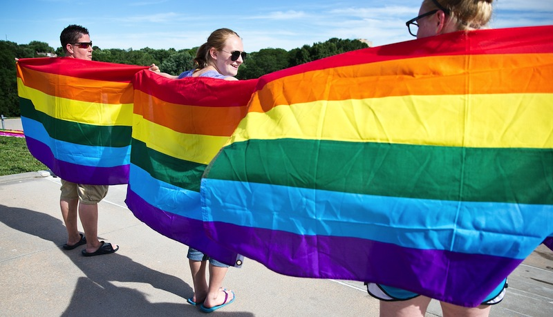 From left, Mel Shartrand, Maddyson Maddox and Makayla Maddox hold up gay rights flags during a gathering at Memorial Park to celebrate the Supreme Court rulings on gay marriage on Wednesday, June 26, 2013. (AP Photo/The World-Herald, ) DOMA;MEMORIAL PARK;OMAHA;NEBRASKA;SUPREME COURT