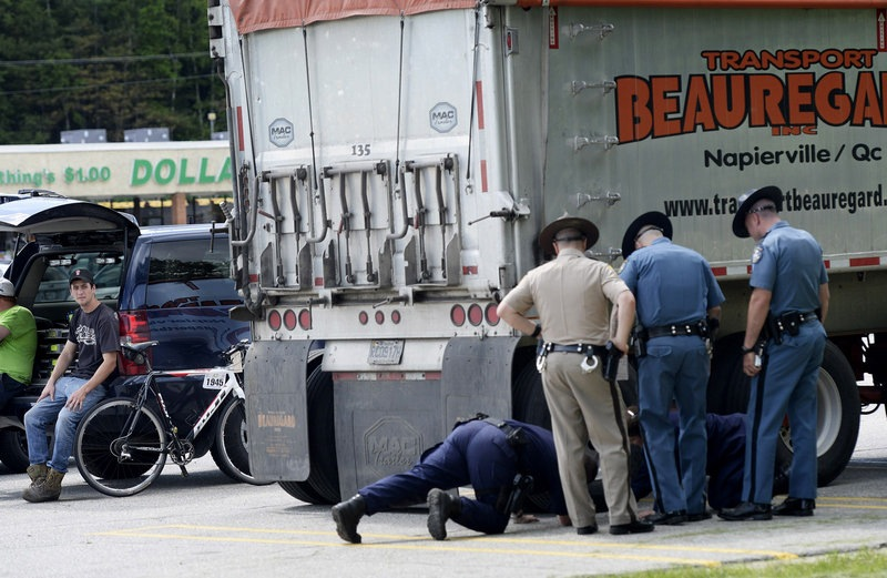 The driver of the tractor-trailer, left, who the police believe was involved in the fatal accident in Hanover, looks on as his truck is inspected by police in Rumford on Friday, June 14, 2013. The bike involved in the collision is leaning against the vehicle.