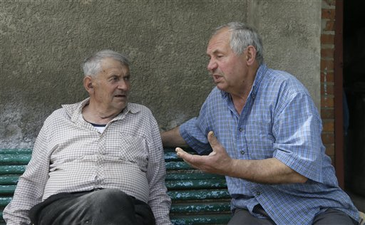 In this May 10, 2013, photo, Heorhiy Syvyi, 78, left, and Ivan Hrushka share their war memories in their home village of Pidhaitsi close to Ukraine's western city of Lutsk. Nearly two dozen civilians, primarily women and children, were slaughtered in Pidhaitsi. Evidence uncovered by AP indicates that Ukrainian Self Defense Legion commander Michael Karkoc's unit was in the area at the time of the massacre.