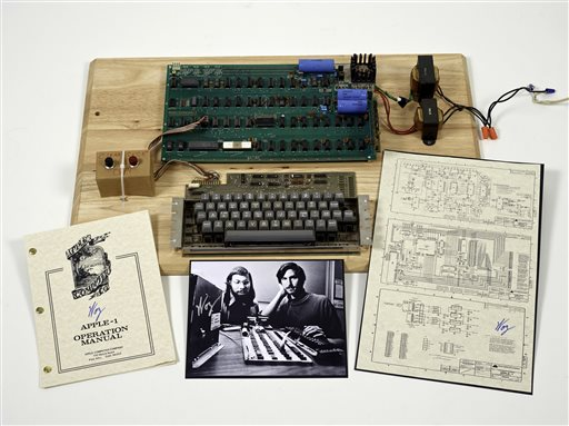 This undated photo provided by Christie's Auction House shows an Apple 1 prototype computer, built in 1976, accompanied by an operation manual and schematic as well as a photo of its inventors, Steve Wozniak, left, and Steve Jobs.