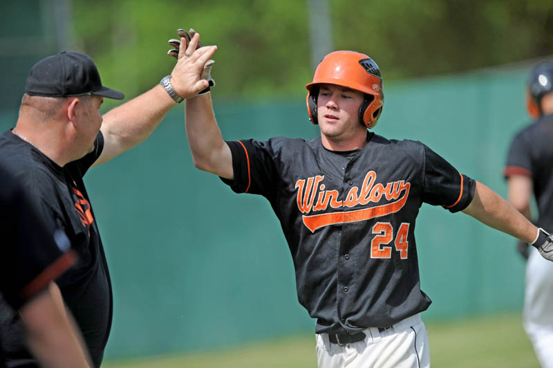 ON THE BOARD: Winslow High School's Dylan Hapworth, right, gets a high five from an assistant coach after crossing the plate for a run in the first inning of the Black Raiders' 7-0 win over Washington Academy in an Eastern B quarterfinal game Thursday in Winslow.