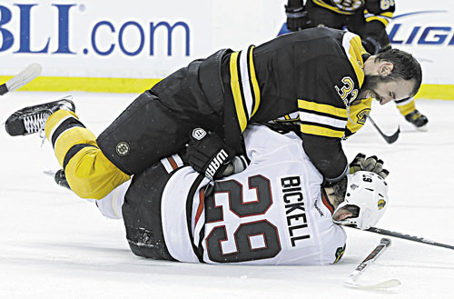BRING IT: Boston defenseman Zdeno Chara (33), takes down Chicago left wing Bryan Bickell during the third period in Game 3 of the Stanley Cup finals Monday in Boston.