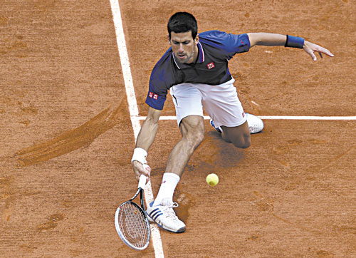 STRETCH: Novak Djokovic returns the ball to Philipp Kohlschreiber during their fourth-round match at the French Open on Monday at the Roland Garros stadium in Paris.