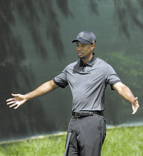 READY TO GO: Tiger Woods talks with a coach on the practice green during a practice for the U.S. Open on Tuesday at Merion Golf Club in Ardmore, Pa.