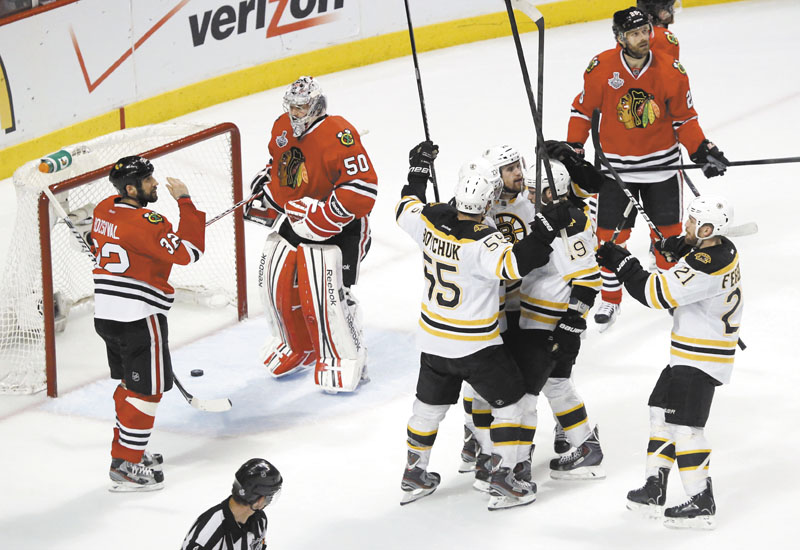 HERE WE GO: The Boston Bruins celebrate a second-period goal against Chicago Blackhawks goalie Corey Crawford (50) as defenseman Michal Rozsival (32) watches during Game 2 of the Stanley Cup Finals on Saturday in Chicago. Boston was badly outplayed in the first period, but managed to rally and win in overtime to even the series at 1.