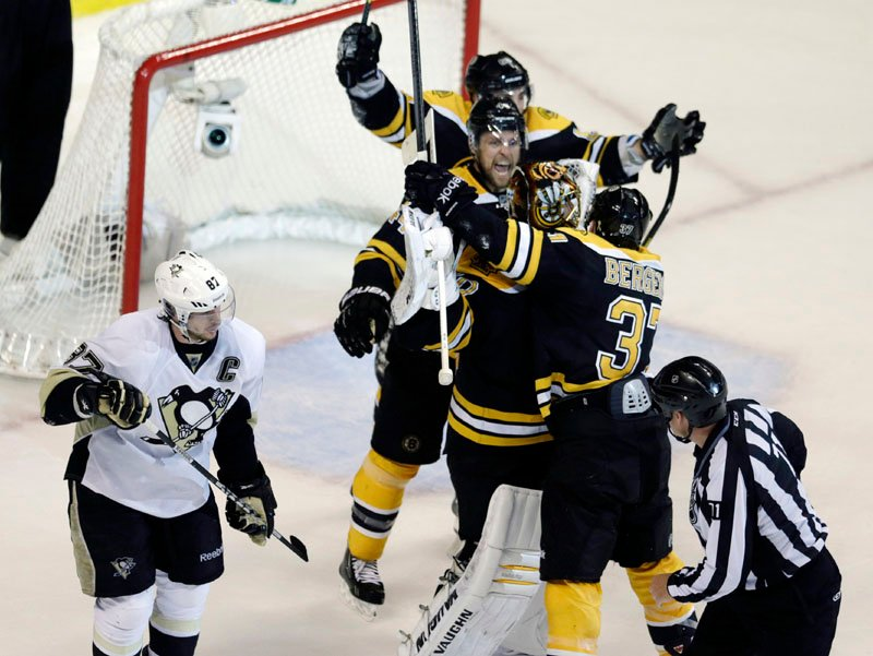 BIG-TIME WIN: Boston's Patrice Bergeron embraces goalie Tuukka Rask as Pittsburgh Penguins center Sidney Crosby (87) skates away after the Bruins won Game 4 of the Eastern Conference finals Friday night in Boston. The Bruins swept the series, 4-0, to advance to the Stanley Cup finals.