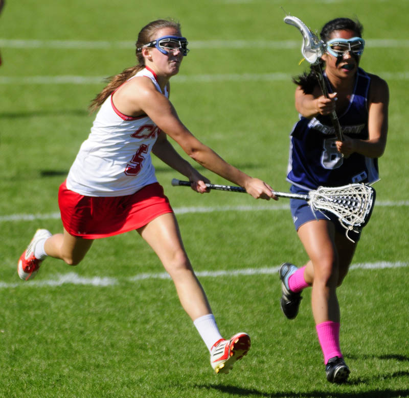 A GOAL: Cony's Emily Quirion, left, follows through on a shot which Portland defender Quinn Lavigne tries to stop during the Rams' 12-8 win in an Eastern A quarterfinal Wednesday in Augusta.