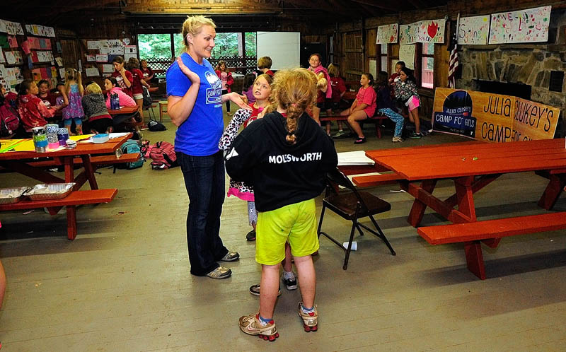 POSITIVE ROLE MODEL: Julia Clukey, center, chats with campers Thursday at Julia Clukey's Camp for Girls at Camp KV in Readfield. An Olympic luger, Clukey hopes to deliver a positive message and encourage confidence in the campers.