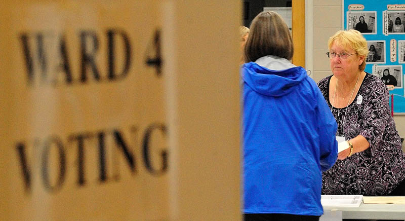 Co-warden Pat Seigny, right, hands a ballot to a voter on Tuesday June at the Ward 4 polling place in the Cony Middle School music room in Augusta.