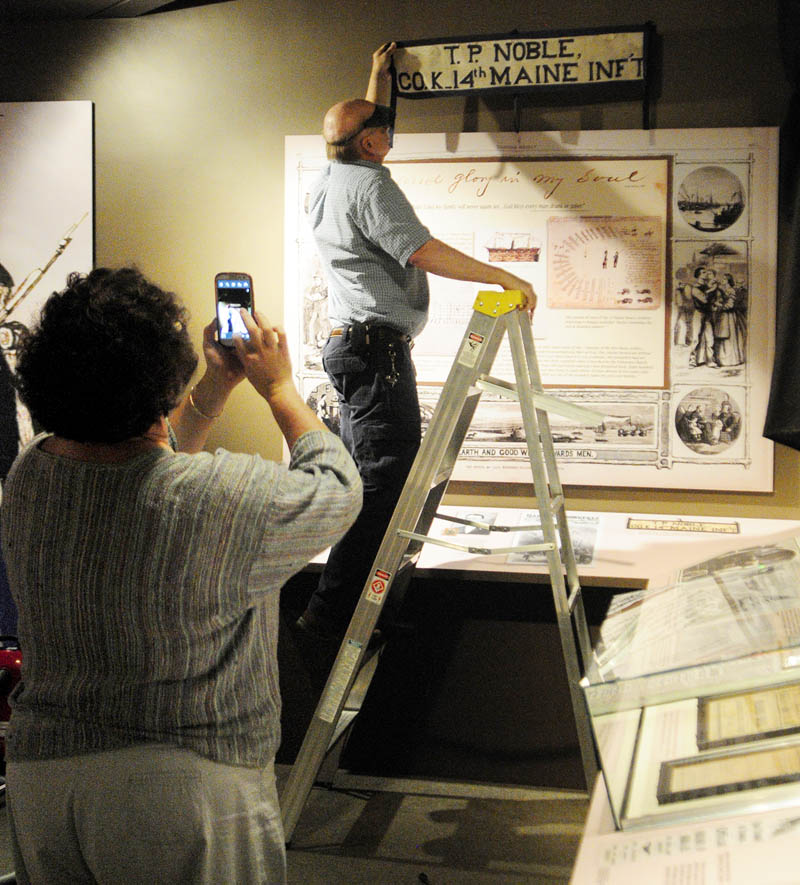 "Curator Laurie LaBar, left, takes a photo of where graphic artist Don Bassett is positioning a banner for the exhibit titled ""Maine Voices from the Civil War,"" on Wednesday at the Maine State Museum in Augusta."