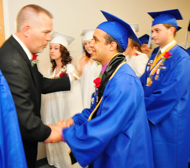 Associate Headmaster Jamie Soule, left, shakes hands with Jaun Cosme before Erskine Academy's commencement on Friday at the Augusta Civic Center.