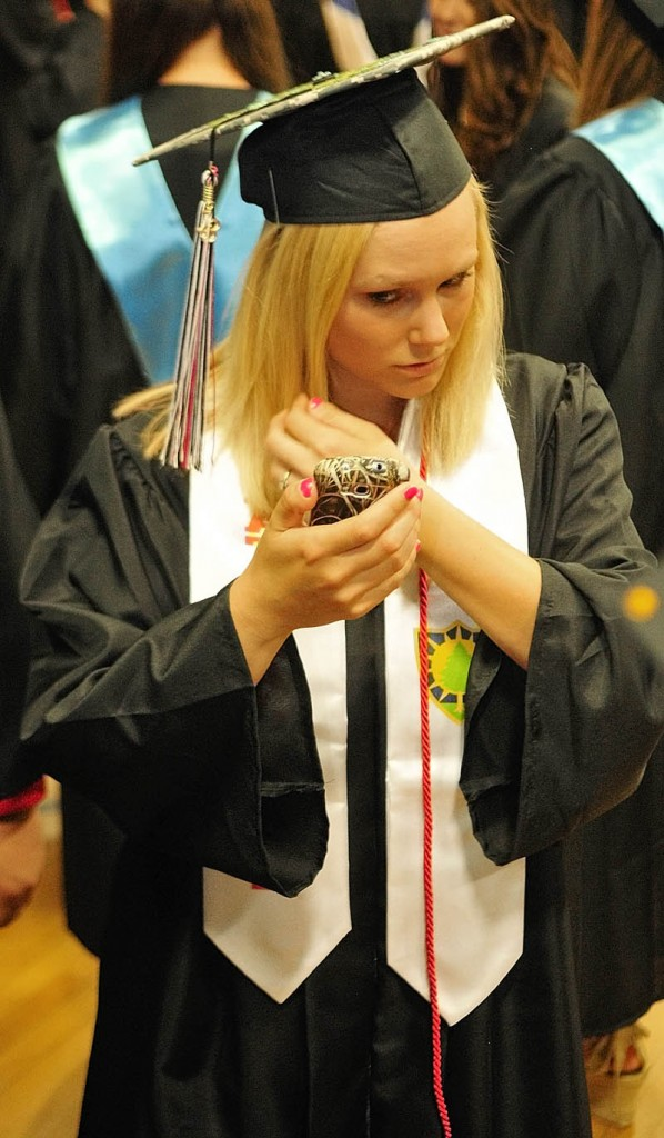 Wearing a white Maine National Guard sash, Courtney Pierce checks her reflection on the screen of her phone before the Hall-Dale High School commencement ceremony on Saturday at the school in Farmingdale. Pierce, 19 of Farmingdale, said that she plans to be a mechanic with the guard.