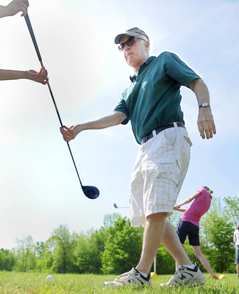 St. Michael teacher John Hickey hands a driver back to a student during a class golf outing on at Western View Golf Club in Augusta on May 31.