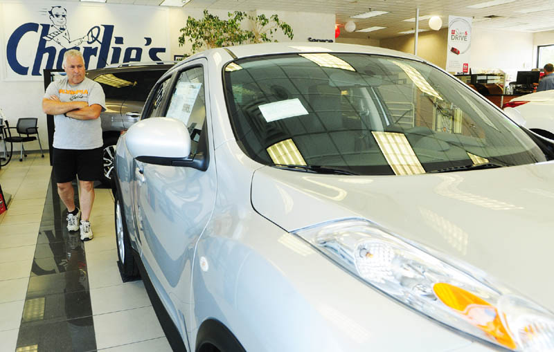 Dana Timberlake looks over a Nissan on Friday at Charlie's Motor Mall in Augusta. Automotive sales, which account for about a third of the area's taxable sales, are leading a surge in the local economy, according to business people.