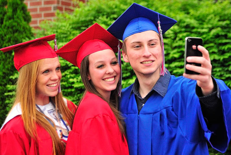 Emily Deering, left, Zoe Nielsen and Andrew Knoedler pose for a shot with his smart phone before Messalonskee graduation on Thursday at the Augusta Civic Center.