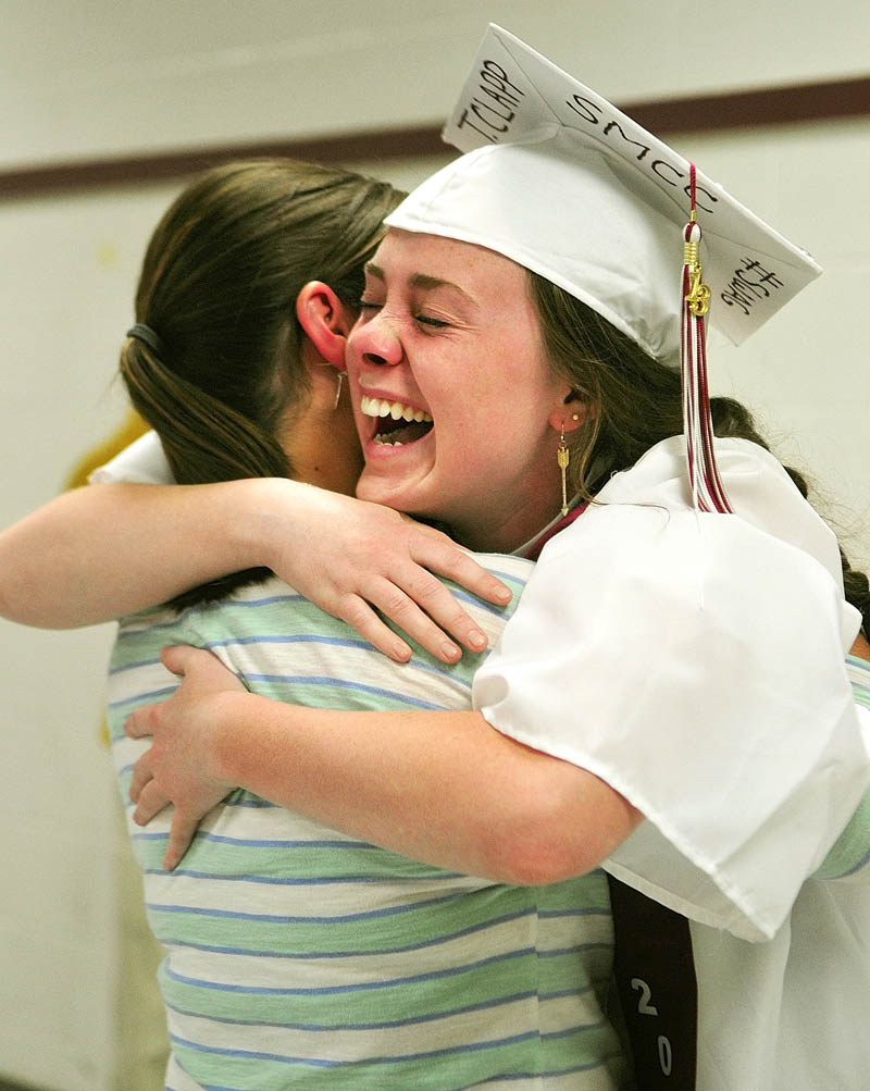 Senior Taylor Clapp, left, hugs her old friend, Sarah Spofford, of Greenfield, Mass., who surprised her by showing up at her graduation ceremony on Saturday at Richmond High School.