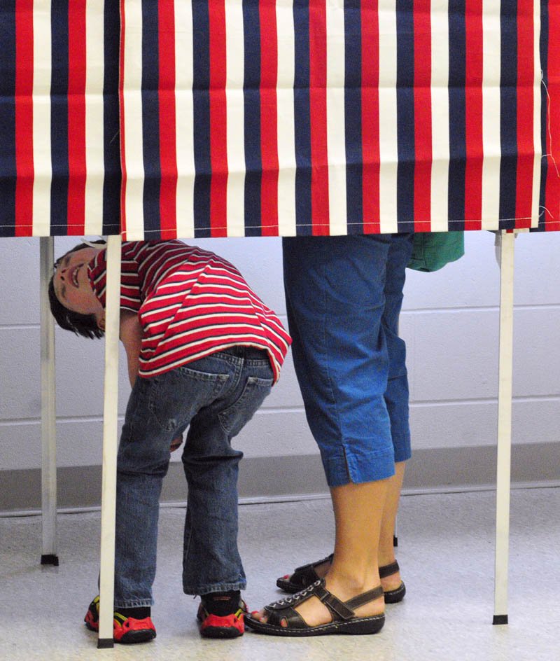 Samuel Goldey, 7, looks up at his mother, Anya Goldey, while she casts a ballot on Tuesday at the Ward 4 polling place in the Cony Middle School music room in Augusta.