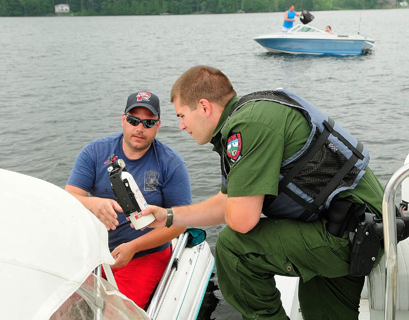 Deputy Game Warden Harry Wiegman checks the fire extinguisher on Steve Sirios' boat while doing a safety check on Wednesday on Messalonskee Lake.