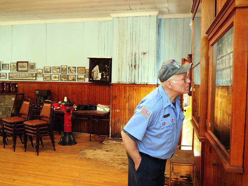 Hallowell Fire Department Engineer Norman Cormier looks at photos in a display case in the upstairs meeting room on Tuesday, during a tour of the Hallowell Fire Station. The marks on the wall and floor behind him are creosote and mold stains caused by roof leaks.