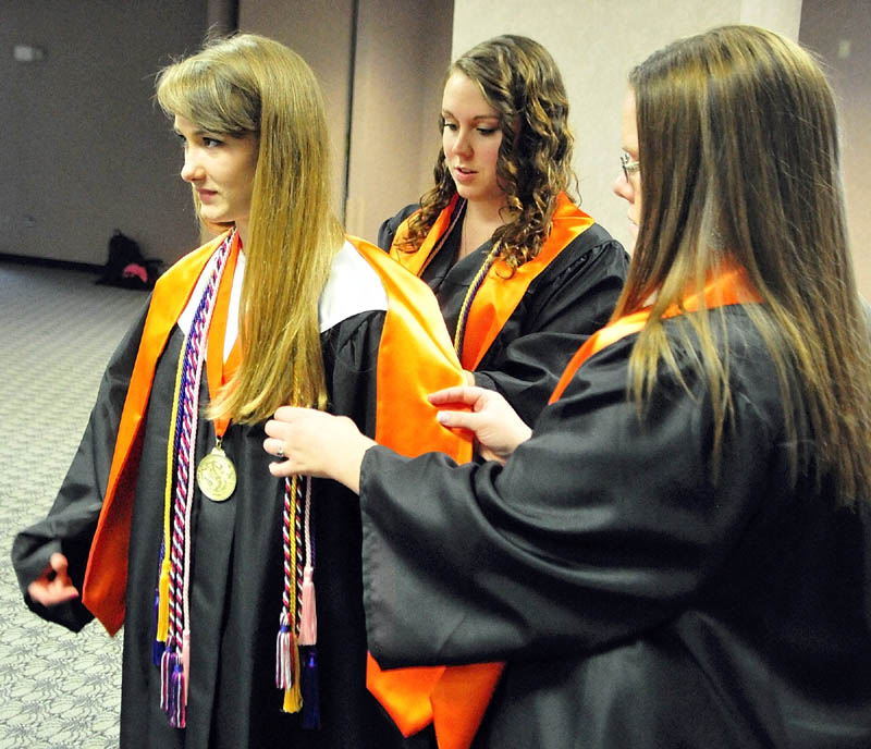 Salutatorian Hannah Morgan, left, gets a hand with her regalia from Emily Kobrook, center, and Paige Hinkley, before the Gardiner Area High School commencement ceremony on Saturday at the Augusta Civic Center.