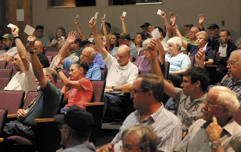 Farmingdale residents vote to continue the discussion of Article 10 at the annual town meeting at Hall-Dale Middle School on Saturday.