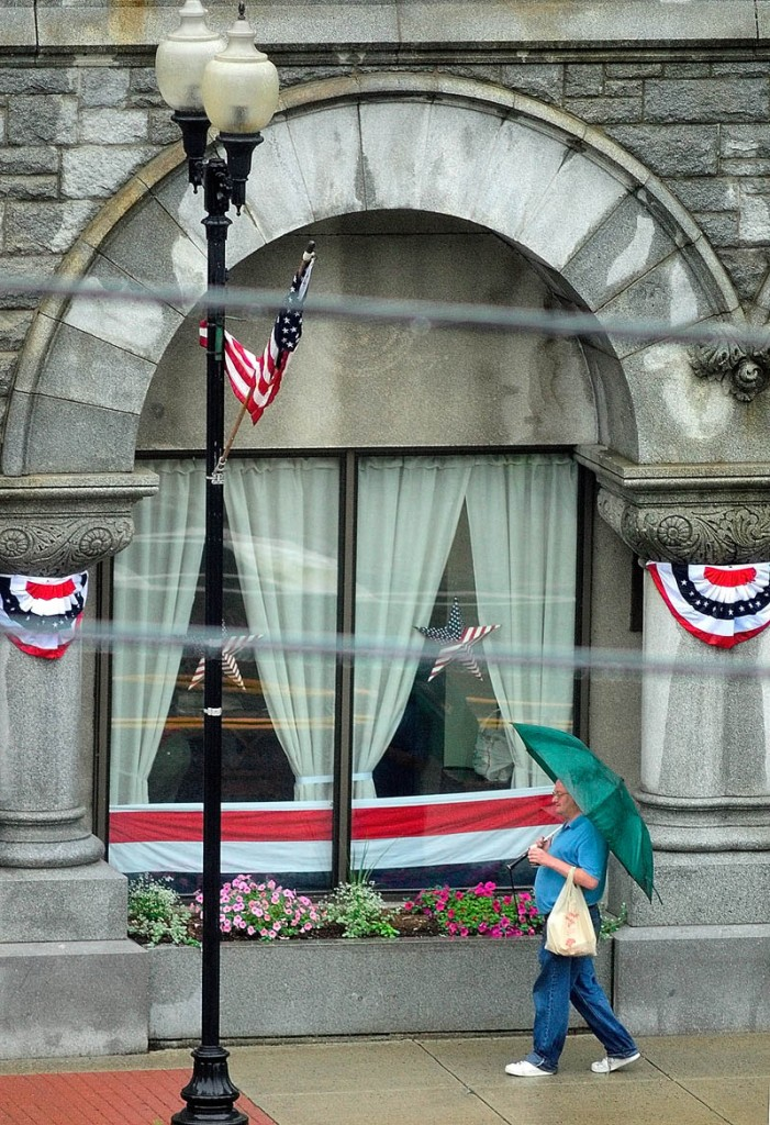 An umbrella-wielding pedestrian walks past bunting-draped window and pillars on Friday in front of the Olde Federal Building in Augusta. The large, granite office building is at the corner of Winthrop and Water Streets in downtown Augusta.