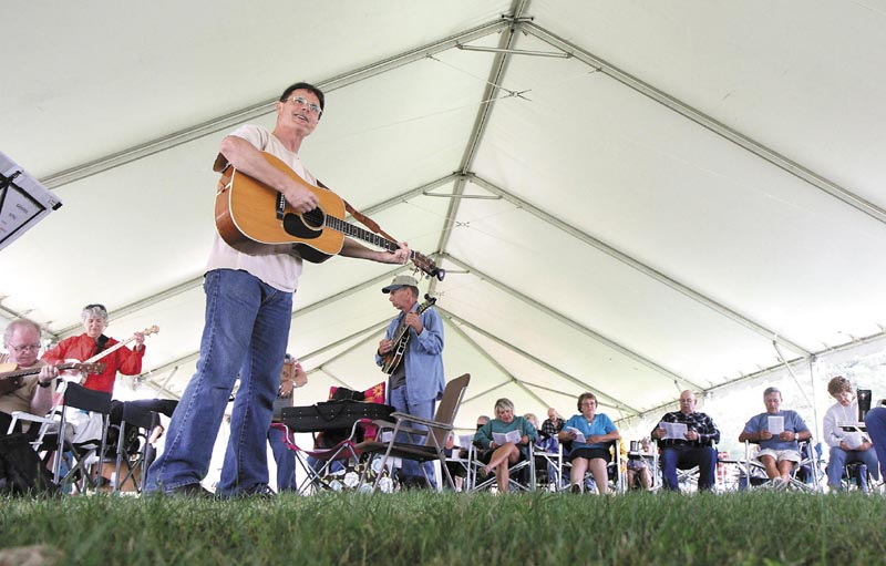 Mike Robinson, of Belchertown, Mass. leads in the singing some hymns under the big tent on Sunday morning at the 40th Blistered Fingers Bluegrass Festival at the Litchfield Fairgrounds. Robinson and his wife, Mary, not shown, travel the country to bluegrass festivals to share the gospel both in word and in song.