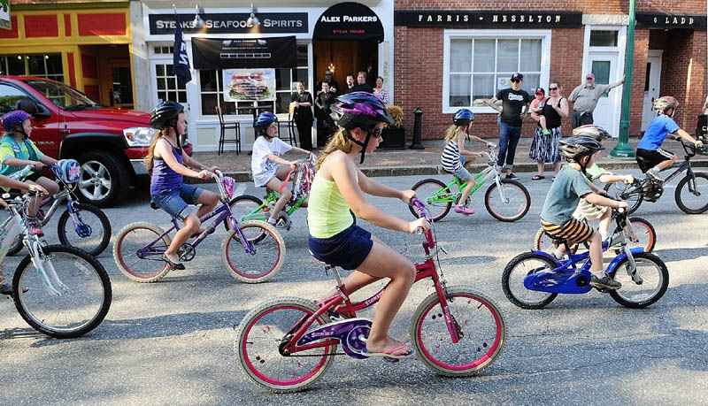 Children ride bicycles down Water Street on Saturday in downtown Gardiner as part of the 4th annual Ride into Summer. The event included a motorcycle ride around town, peoples' choice pizza contest of local traditional and non-traditional pizzas, live music, and was capped off with a fireworks display along the Kennebec River.