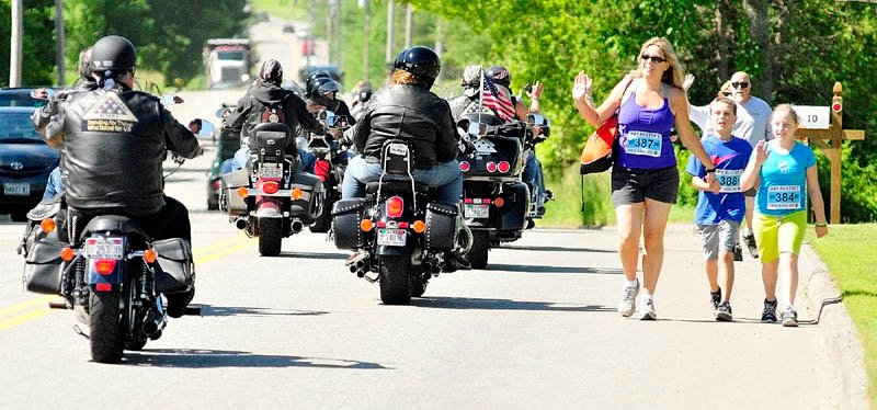 A group of motorcyclists, cruising to VA Maine Healthcare Systems-Togus for the 12th Annual Togus Veterans Car Show, and walkers, taking part in the Amy Buxton's Underdog Jog Memorial 5K Run and Walk, wave at each other as they cross pathes on Cony Road on Saturday in Augusta. Proceeds from the run/walk event, which began and ended at Cony High School, were to benefit Almost Home Rescue, the Kennebec Valley Humane Society and the Family Violence Project.