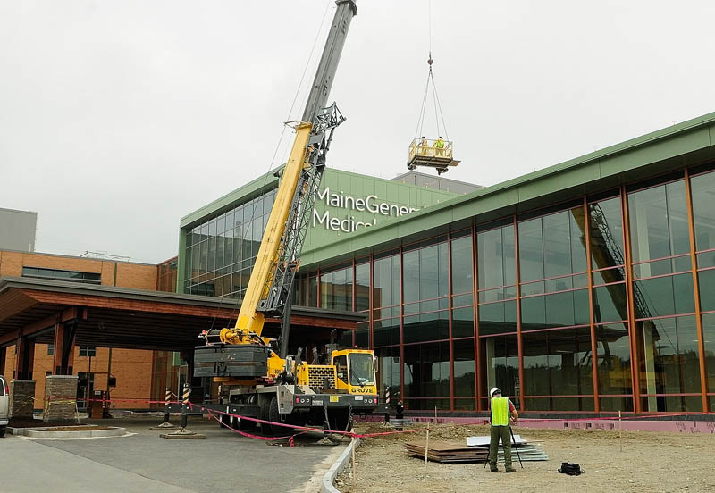 A crane lifts workers up to clean the walls around the recently mounted sign letters on top of the Alfond Center for Health regional hospital, to be operated by MaineGeneral Health, on Wednesday in Augusta.