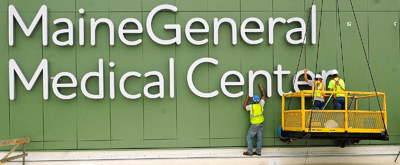 Workers clean the walls around the recently mounted sign letters on top of the Alfond Center for Health regional hospital, to be operated by MaineGeneral Health, on Wednesday in Augusta.
