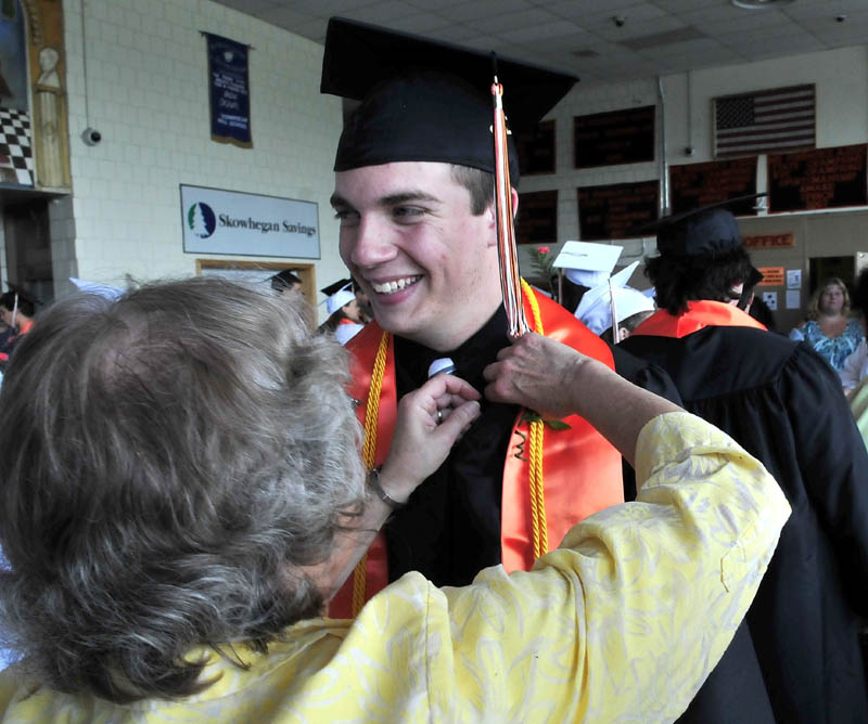 Skowhegan Area High School graduate Cory Palmer smiles as Eleanor McClay struggles to pin a corsage on him prior to commencement on Sunday.