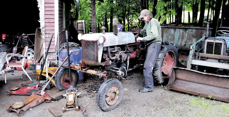 Keith Melancon fires up his older model tractor at his Town Farm Road home in Farmington. Melancon said people have complained about the vehicles and equipment on the property.