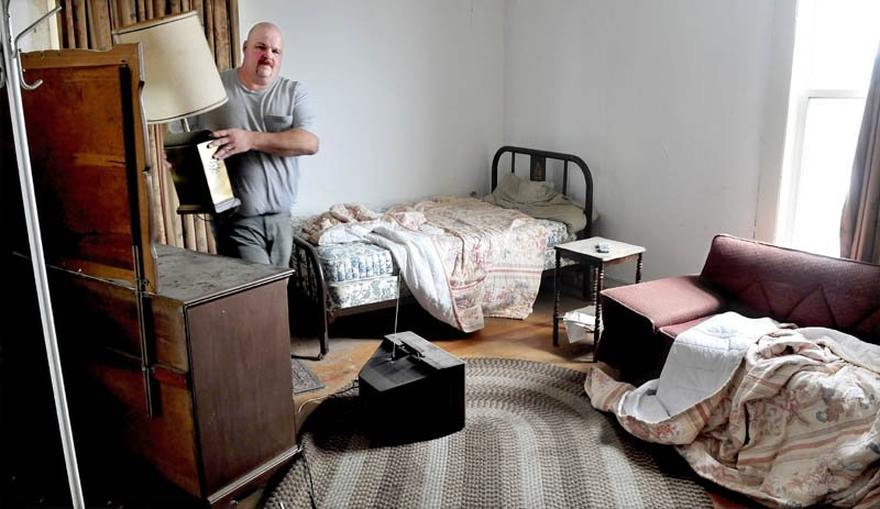 Marc Wheeler removes a brass lamp that will be salvaged, after other items are disposed of, from a room on the second floor of the former Kennebec Valley Inn in Skowhegan, on Tuesday. Wheeler and his wife, Janet, plan to open the Blue Moon Lounge this summer and renovate sections of the building for future banquet events.