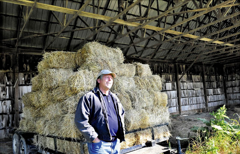 Richard Hopper, president of Kennebec Valley Community College, speaks beside a hay wagon in an unused barn at the Alfond campus in Hinckley on Wednesday. The section, in one of three barns, will be used to store farm equipment, while another section will have labs and classrooms for sustainable agriculture courses.