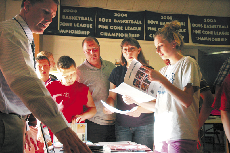 Mona Bussell, 16, right, browses through an academic catalog for Maine Central Institute, along with her parents, Cory and Jean Bussell, as they speak with Dean of Admissions Clint Williams, left. MCI was one of seven schools at a high school fair in Athens Monday evening.