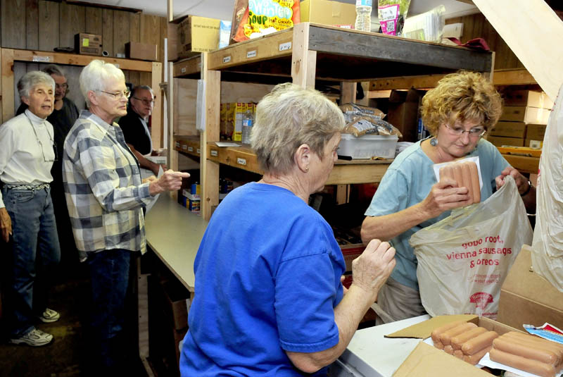 Interfaith Food Pantry volunteers in Fairfield work in a cramped room, filling requests for food on Thursday. A $25,000 pledge in matching funds made recently will help in the goal of $100,000 for a larger facility. From left are Louise O'Brien, Shirley Fenlason, Kathy Keup and Arlene Toulouse.