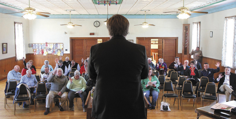Residents vote on an article as moderator David Benier presides over the annual Benton Town Meeting inside the Benton Grange Hall recently.