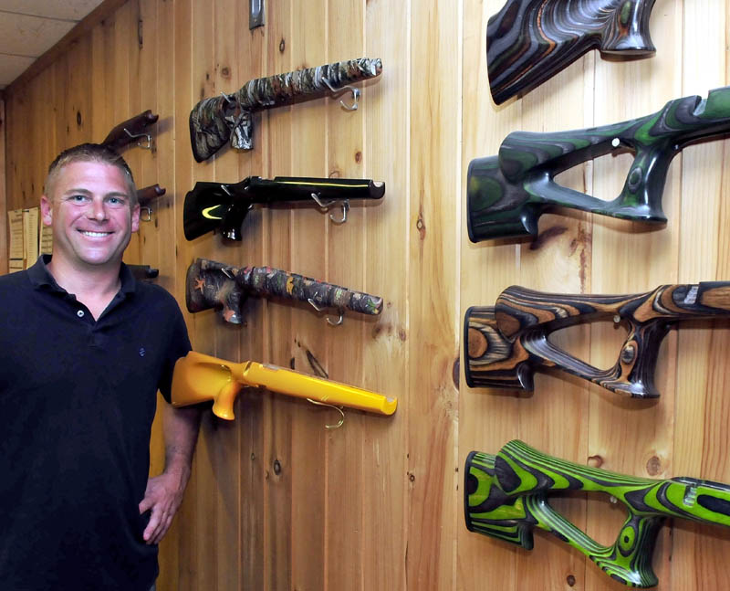 Cousineau Wood Products Vice President Brody Cousineau on Monday stands next to some of the wood veneer gun stocks made at the North Anson company.