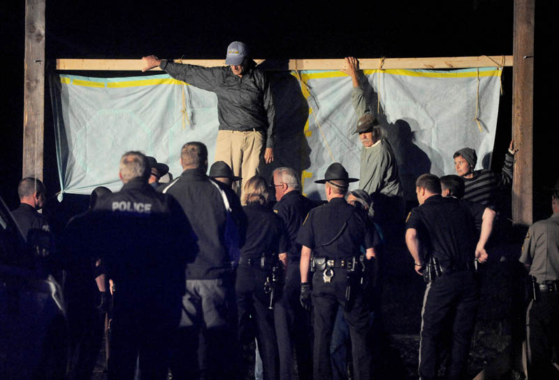 Authorities approach members of 350 Maine atop a scaffold that blocked the railroad crossing at Lawrence Avenue in Fairfield Thursday night, to protest the transport of fracked oil on the line.
