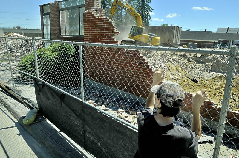 Jon Duffy watches as the final pieces of St. Francis de Sales Church in Waterville are brought down Wednesday. He said he gathered there with others to witness the passing of the old church. Several reasons including high maintenance costs led to the demolition of the church, which was finished in 1874. A three-story housing complex will go up at the site and is expected to be completed in June 2014.