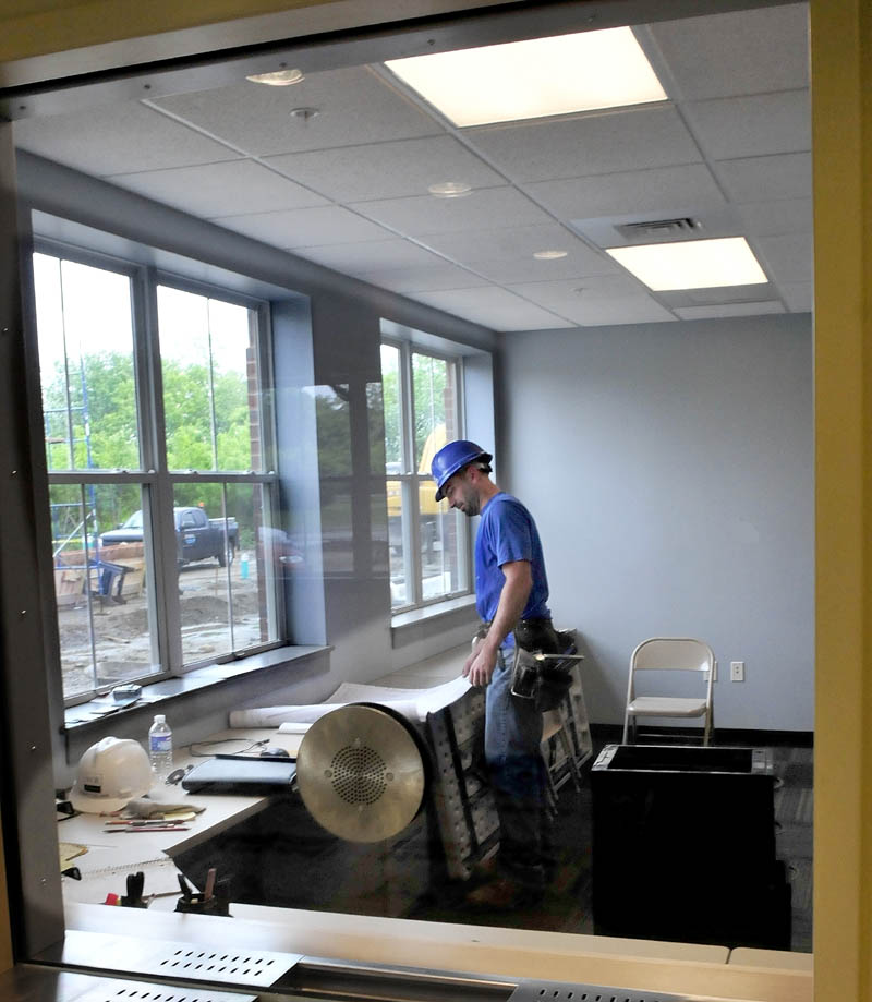 Construction worker Ian Deforge looks over building plans inside the dispatch room in the new Waterville Police Department station on Wednesday.