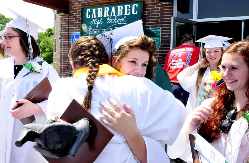 Carrabec High School graduates Michaela Forsten, facing camera, hugs Courtney Frost after graduation ceremonies in North Anson on Sunday.