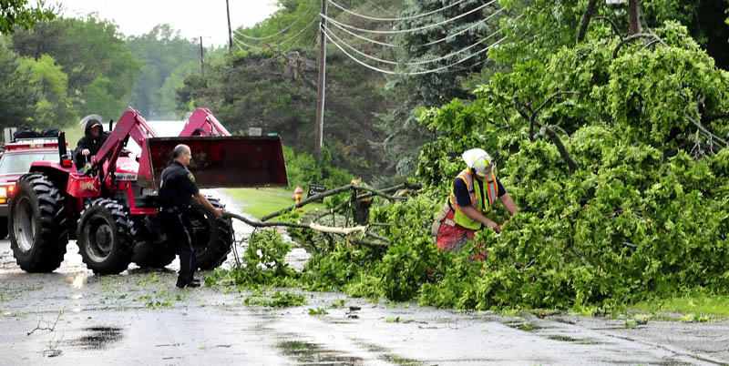 Clinton police officer Stanley Bell, center, pulls limbs away as a Clinton firefighter uses a chainsaw to cut up a tree that fell and blocked a lane on the Hill Road, following a fast-moving storm Tuesday afternoon. At left, neighbor Don Burnham uses his tractor to help.