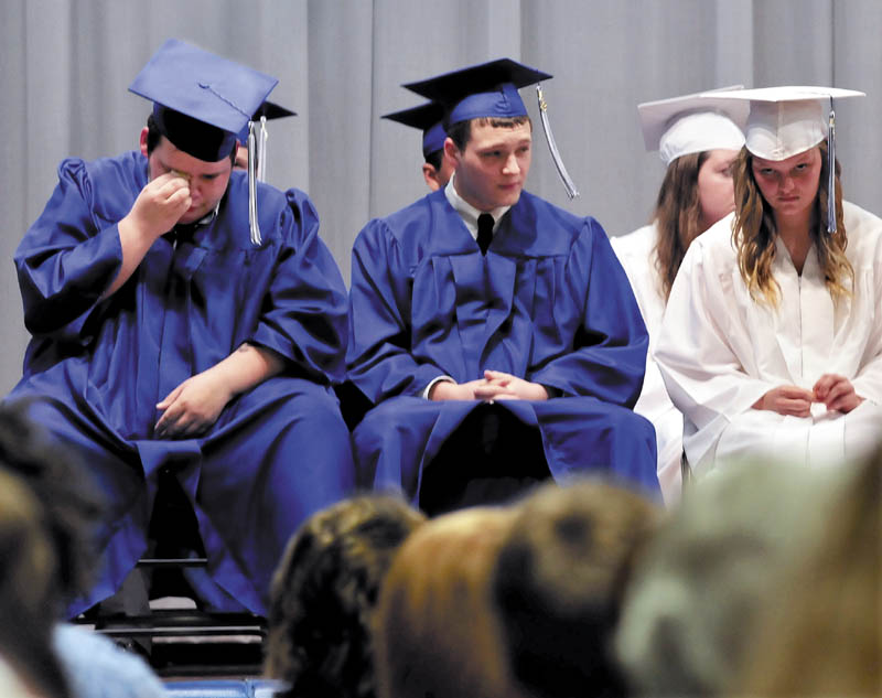 Upper Kennebec Valley Memorial High School student Trevor Beane wipes away a tear while listening to speakers fondly talk about the 13-member graduating class during commencement on Sunday in Bingham.