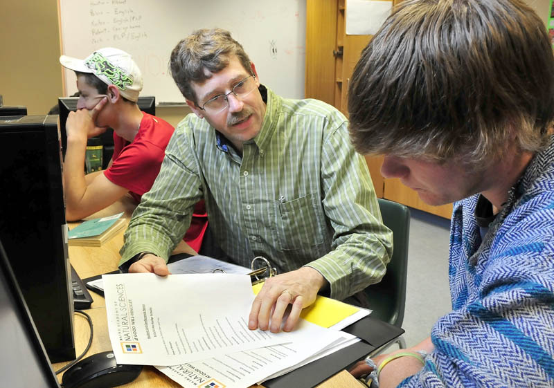 Troy Frost, co-director of the Maine Academy of Natural Sciences, on Thursday speaks with students Keifer Schulz, right, and Jonathon Mullen. Frost is one of five Mine educators to receive the Commissioner's Recognition Awrad from the Department of Education.