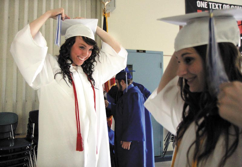 Courtney Taylor, left, looks over at Alexander McClintock, right, as they adjust their caps before the start of commencement exercises at Madison Area Memorial High School on Friday night.